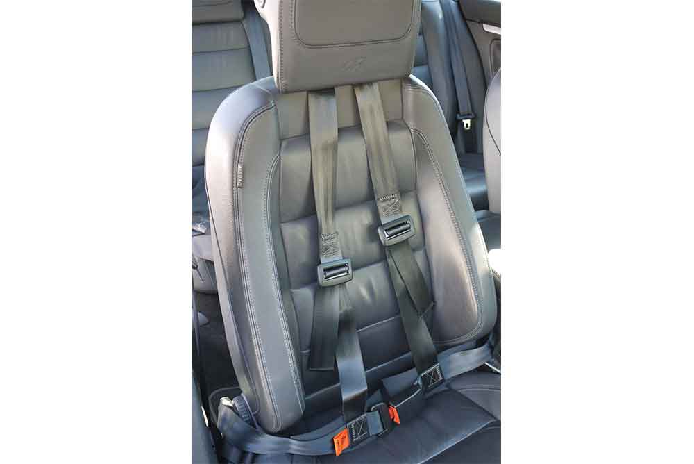Postural harness fitted to a car seat