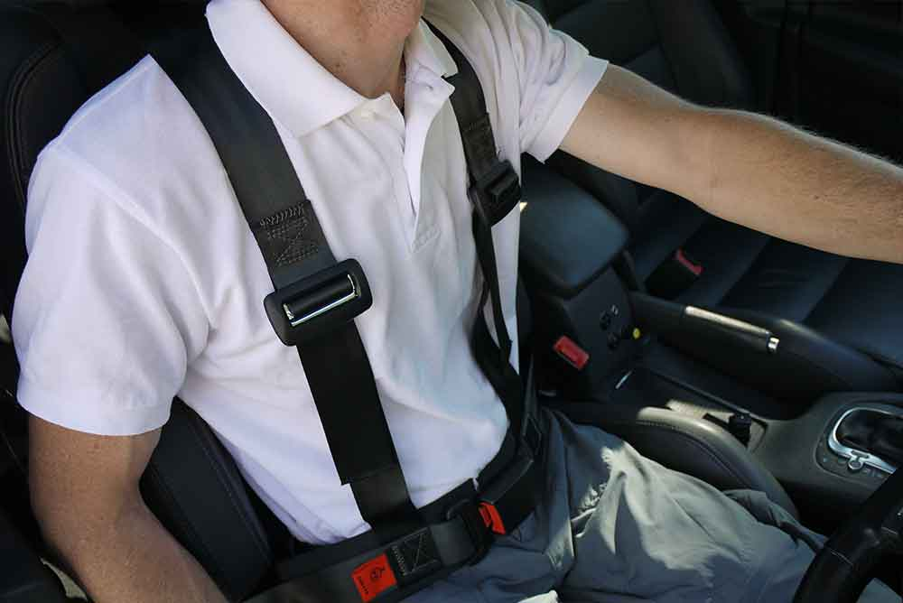 man wearing a postural harness whilst seated in a car seat