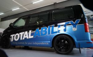 Side View of black van with Total Ability logo and driving controls for your independence tagline