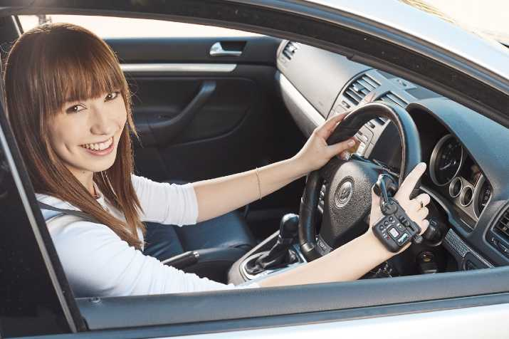 Smiling female driver seated in car driving with Satellite Accelerator hand controls from Total Ability