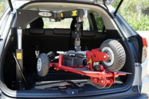 SG50 Hoist from Fadiel lifting a red scooter into the boot of a hatchback car