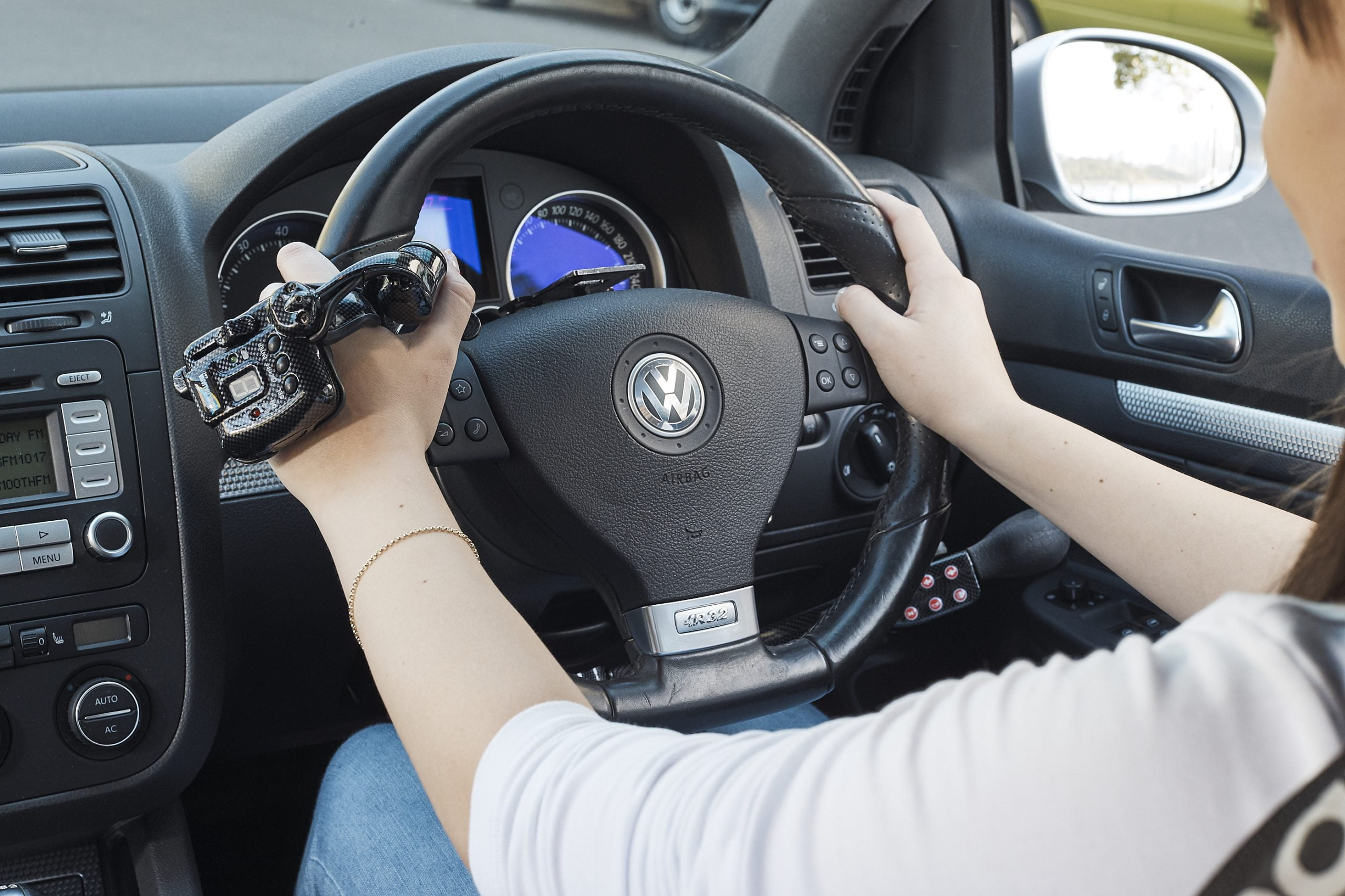 over shoulder view of lady driving with wireless satellite accelerator hand control