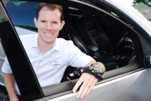 Man in wheelchair leaning on open car door