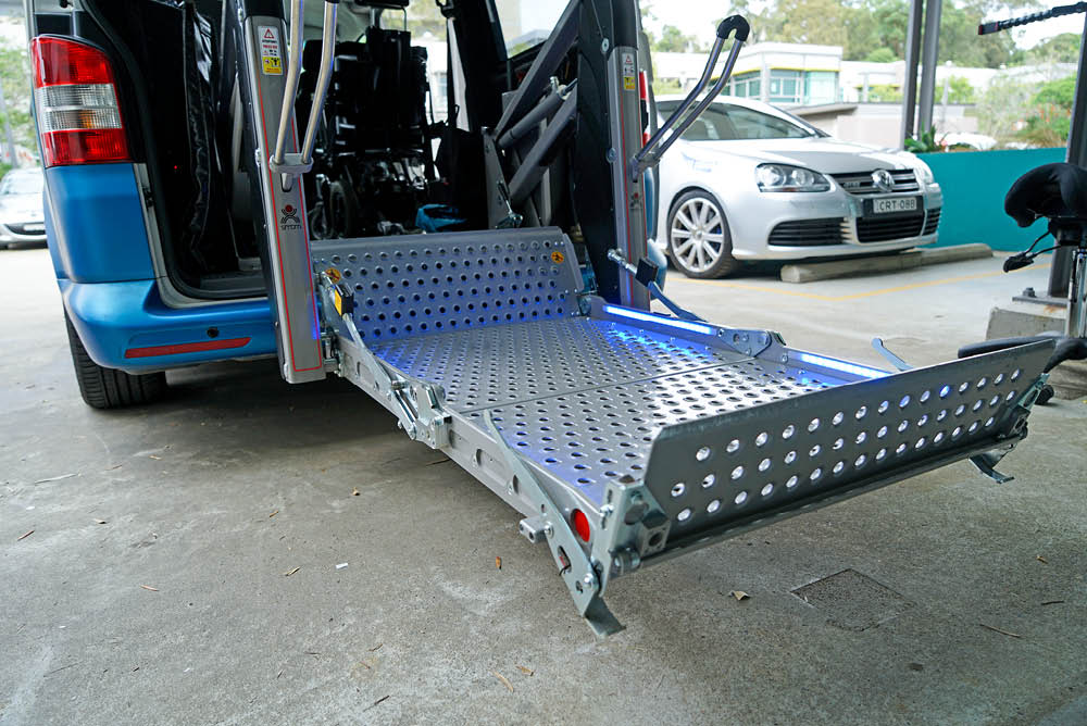Platform lift unfolded at the back of a van - angled side view