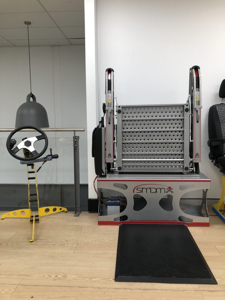 Demo stand with hand controls on the left and Fadiel Italiana Platform Lift on a demo stand on the right
