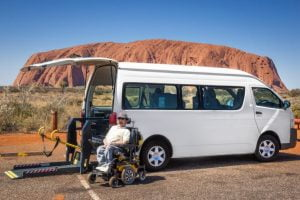 Van parked in front of Uluru with a man in a wheelchair sitting in front
