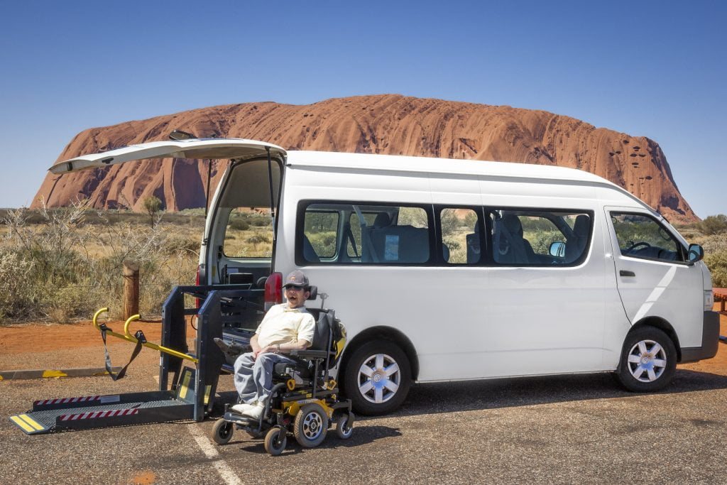 Van parked in front of Uluru with a man in a wheelchair and person sitting in front. When personal need transforms into service.