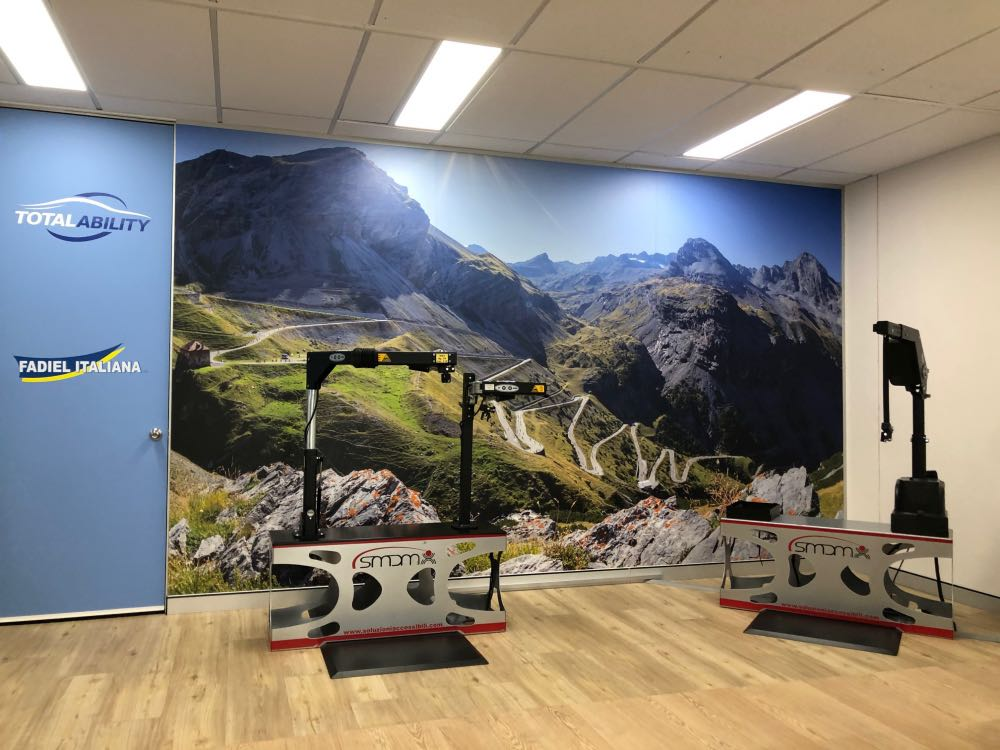 Total Ability showroom with Stelvio image on wall with wheelchair hoists on demo stands in front and TA and Fadiel logos on door to the left