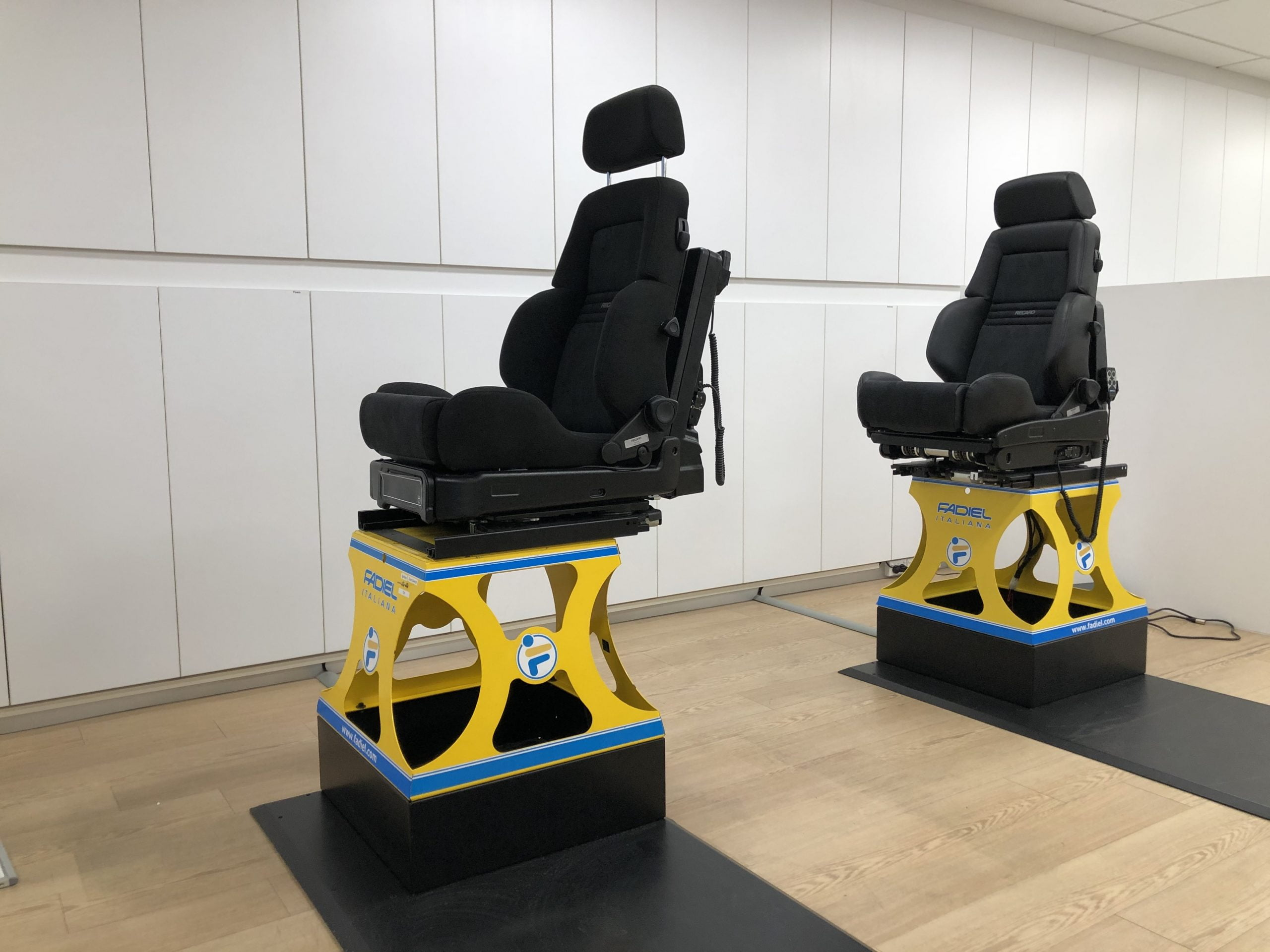 Two Lowering Swivel seats on demo stands. The one on left has reclining ability.