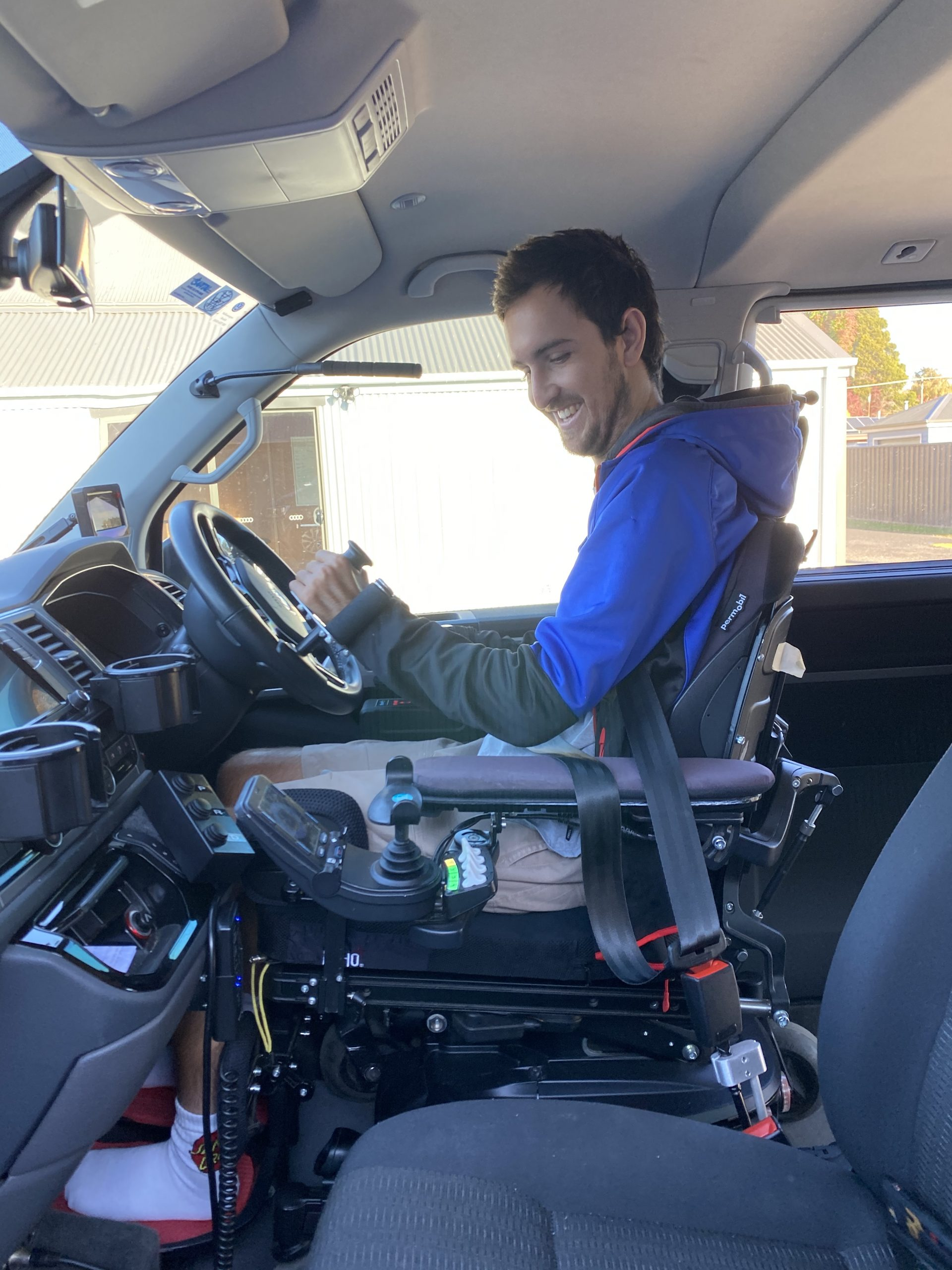 Person with disability smiling in power chair driving from chair with high level driving modifications from Total Ability.